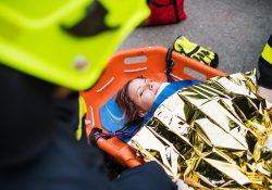 A young injured woman in a plastic stretcher after a car accident, covered by thermal blanket. Close up.