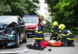 Firefighters helping a young woman after a car accident. A female driver in a plastic stretcher on the countryside road.